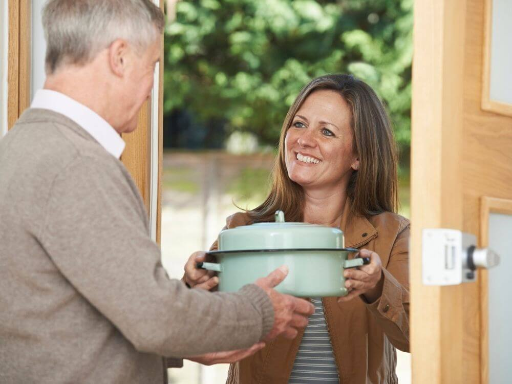 woman-delivering-meal-to-senior-man 8 ways to make your life easier as a church administrator